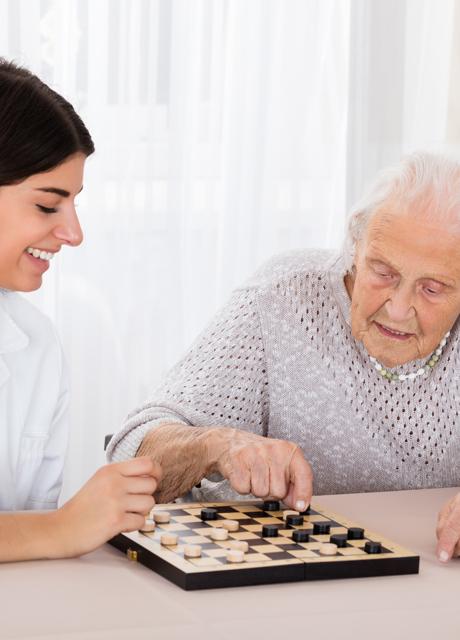 Pflegerin spielt Brettspiel mit älterer Frau