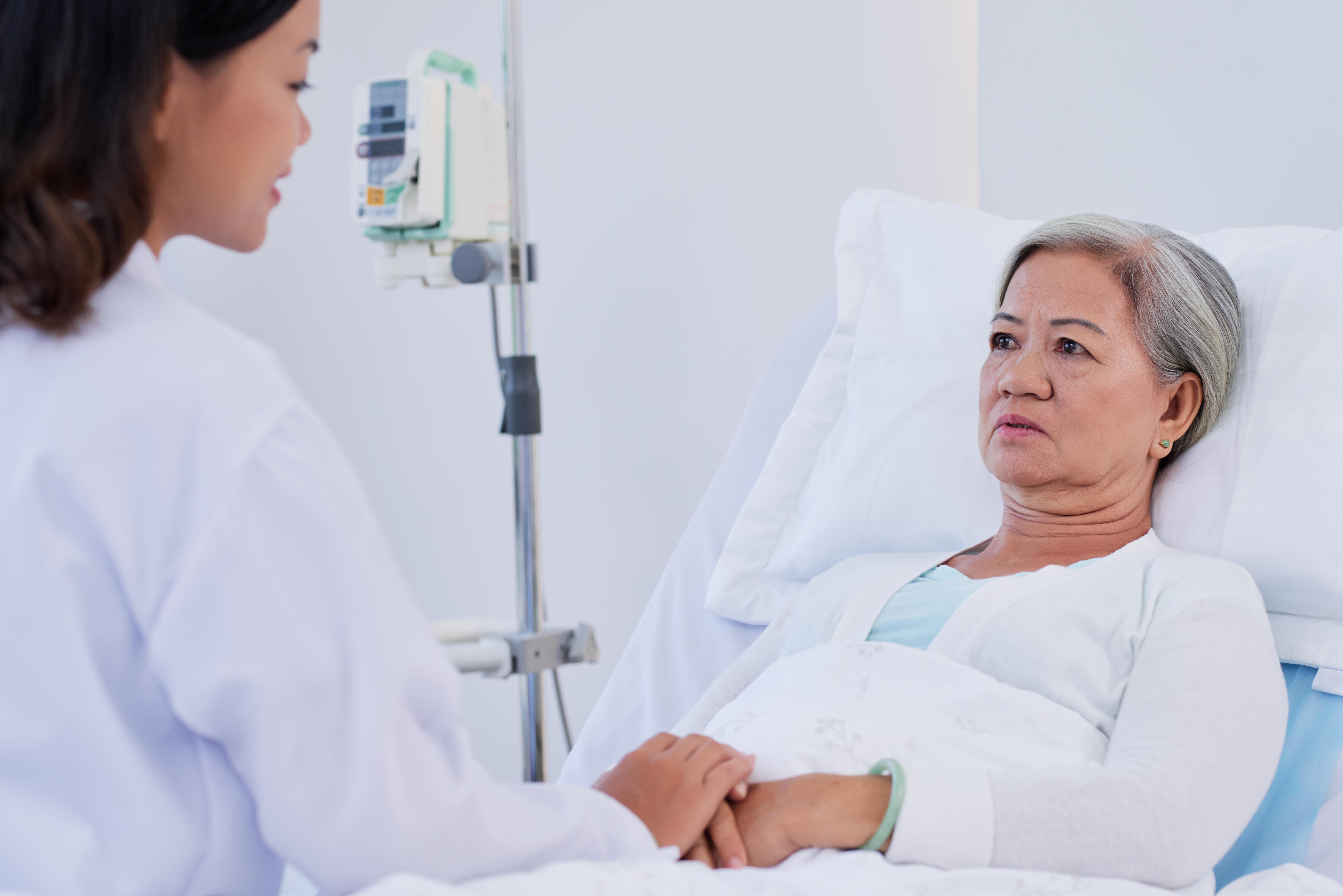 Krankenpflegerin hält Hand einer Seniorin am Spitalbett